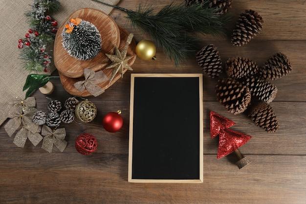 Vista superior da moldura com fundo preto e decoração de natal na mesa de madeira.