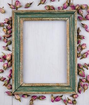Vista superior da moldura dourada esverdeada com botões de rosa roxos secos em uma superfície branca
