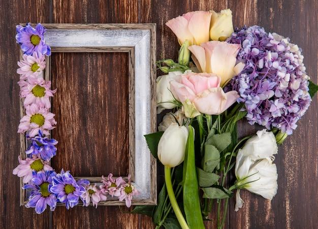 Vista superior da moldura e flores nela e no fundo de madeira com espaço de cópia