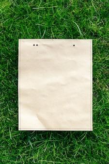 Vista superior da moldura feita de grama verde primavera e embalagens de papel artesanal com espaço de cópia para o logotipo natu ...