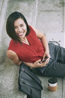 Vista superior da mulher asiática alegre dando um sorriso para a câmera descansando nas escadas