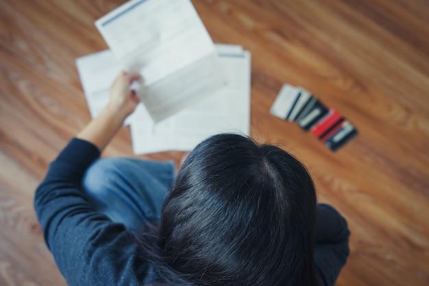 Vista superior da mulher asiática jovem estressada conhecer o problema financeiro e sem dinheiro para pagar a dívida do cartão de crédito.