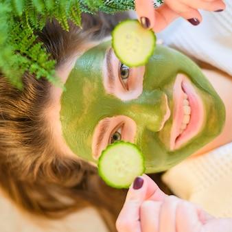 Vista superior da mulher com máscara facial em segurar fatias de pepino