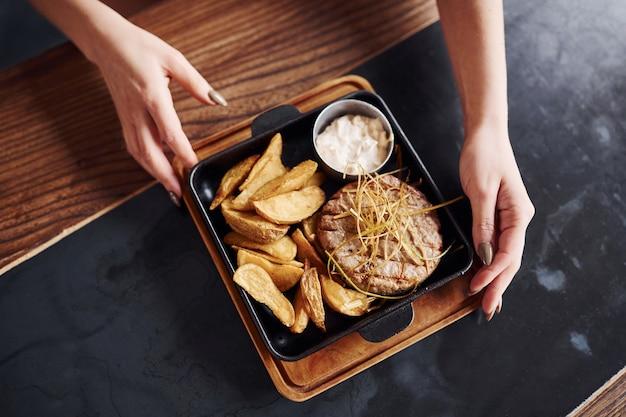 Vista superior da mulher come fast food fresco que está no prato na mesa do restaurante.