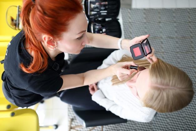 Vista superior da mulher de cabelos vermelhos aplicando blush no rosto do cliente. mulher loira sentada no tratamento de maquiagem. uniforme especial para mua artist. conceito de salão profissional de luxo