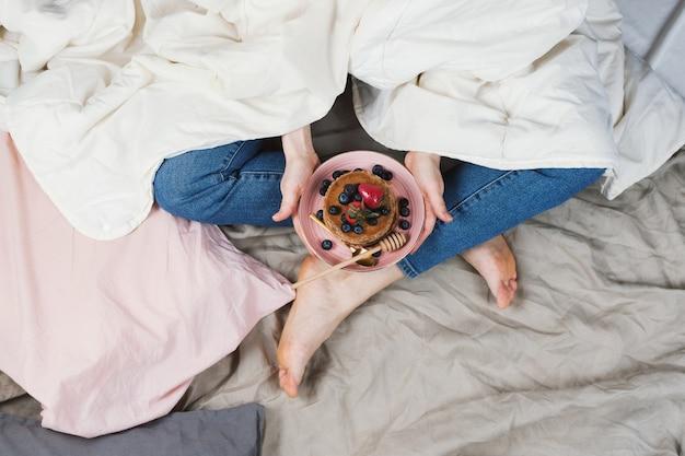 Vista superior da mulher de jeans e camisa branca na cama em um cobertor segurando panquecas de trigo integral vegan