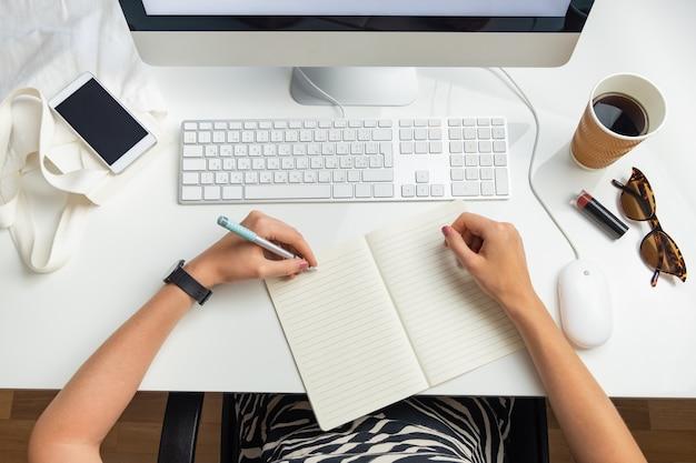 Vista superior da mulher de negócios canhota no escritório minimalista. conceito plano leigo da vida no escritório: pessoa do sexo feminino tomando café na frente do computador desktop no local de trabalho