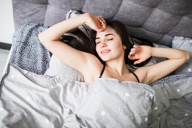 Vista superior da mulher jovem e atraente dormindo bem na cama, abraçando o travesseiro branco macio. adolescente descansando, boa noite conceito de sono.