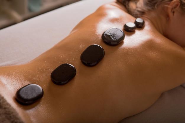 Vista superior da mulher madura relaxante durante massagem com pedras quentes