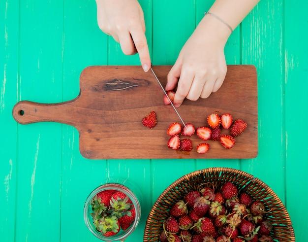 Vista superior da mulher mãos morangos de corte com faca na tábua e morangos inteiros na cesta e tigela na superfície verde