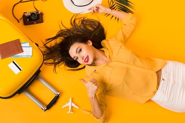 Vista superior da mulher posando ao lado de itens essenciais de viagem