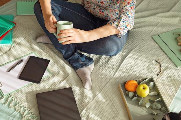 Vista superior da mulher que trabalha em um ambiente informal com seu laptop, bloco de notas, xícara de chá. trabalho remoto, home office, freelancer, conceito de auto-isolamento