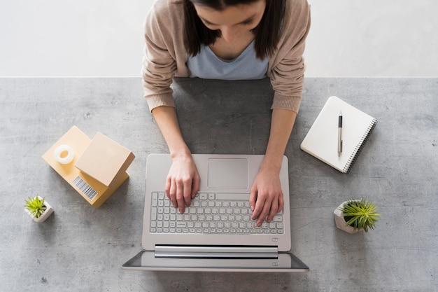 Vista superior da mulher que trabalha na mesa com o laptop