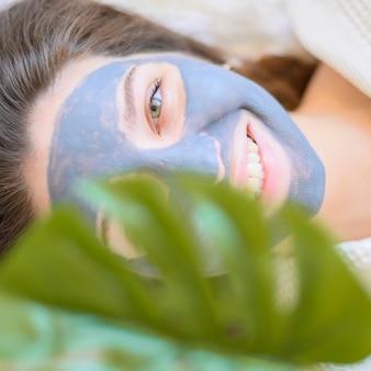 Vista superior da mulher relaxando em casa com máscara facial