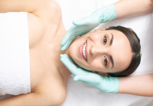 Vista superior da mulher sorridente relaxando e parecendo animada enquanto as mãos da esteticista em luvas de borracha tocam seu rosto