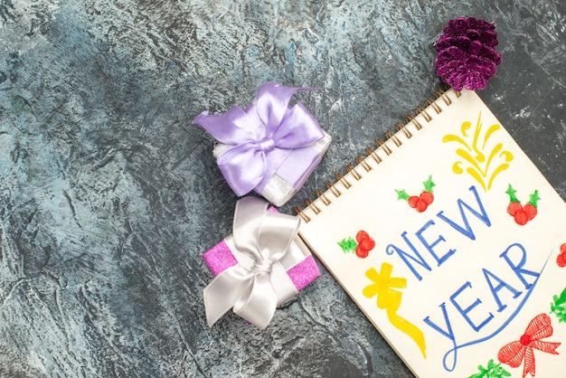 Vista superior da nota de ano novo com lápis e presentinhos na superfície cinza