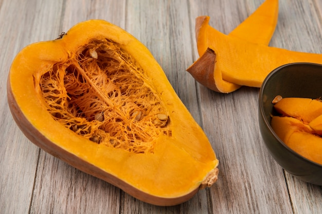 Vista superior da nutritiva meia abóbora com sementes e cascas de abóbora isoladas em uma superfície cinza de madeira