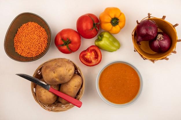 Vista superior da nutritiva sopa de lentilha em uma tigela com cebolas vermelhas em um balde com batatas em um balde com faca com pimentas e tomates isolados em uma parede branca