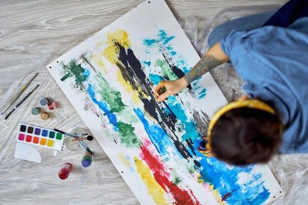 Vista superior da ocupada jovem pintora trabalhando em uma pintura abstrata colorida deitada na