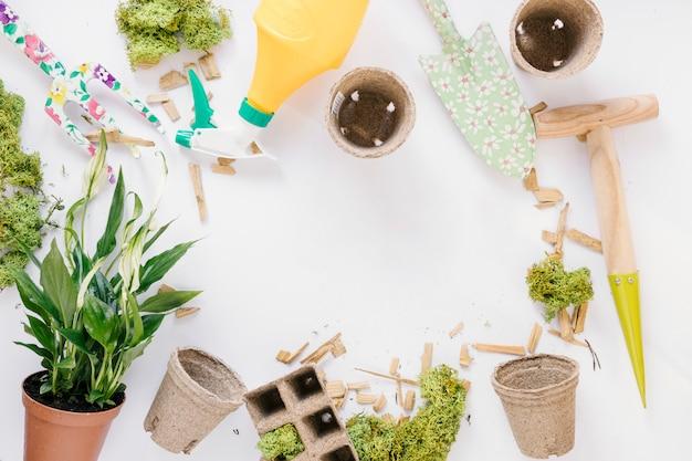 Vista superior da pá; garfo de jardinagem; pote de turfa; vaso de planta; musgo e frasco de spray sobre fundo branco