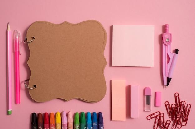 Vista superior da página do caderno em branco com lápis de cor na mesa.