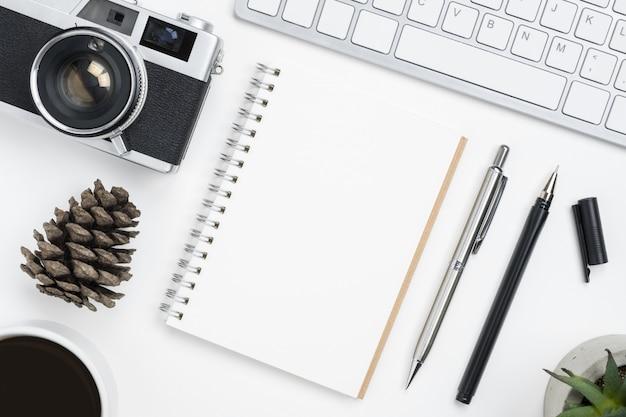 Vista superior da página vazia do caderno na tabela branca do fotógrafo, conceito do planeamento do curso.