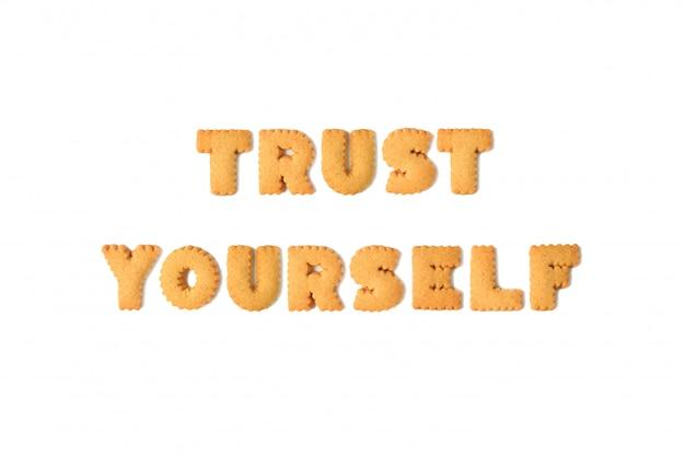 Vista superior da palavra confiar em si mesmo escrito com biscoitos em forma de alfabeto, isolados no fundo branco
