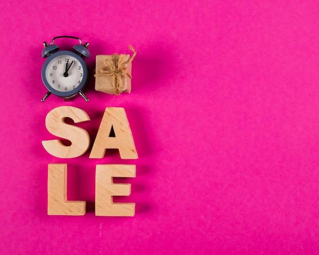 Vista superior da palavra de venda e relógio no fundo rosa