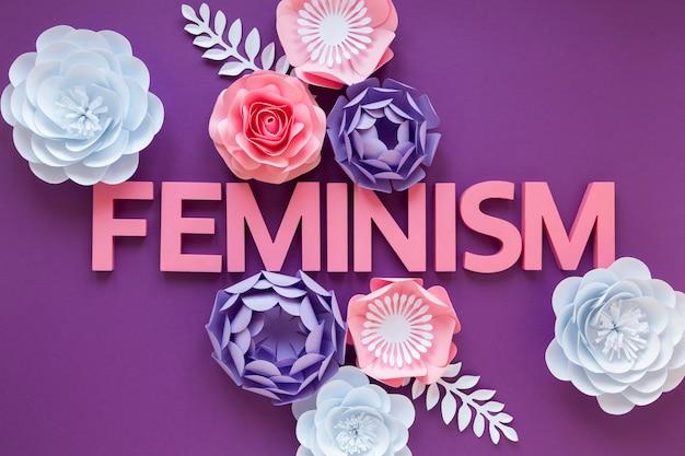 Vista superior da palavra feminismo com flores de papel para o dia da mulher