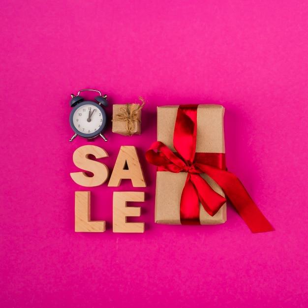 Vista superior da palavra venda e presentes com fundo rosa