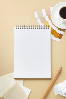 Vista superior da paleta de cores para reforma da casa com caderno e café