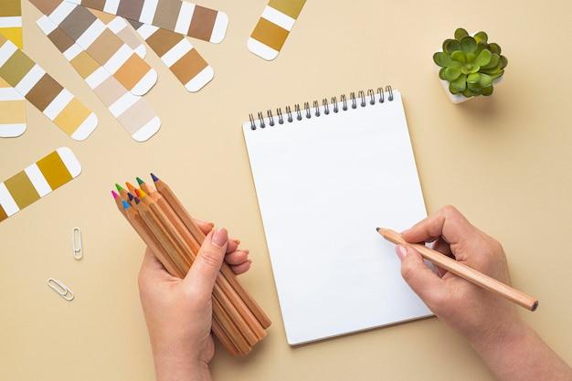 Vista superior da paleta de cores para reforma da casa com caderno e lápis de cor