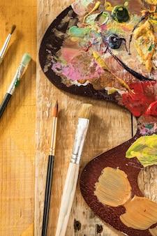 Vista superior da paleta de tinta com pincéis e tinta