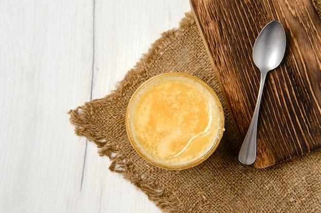 Vista superior da panela com mel e colher na tábua de madeira
