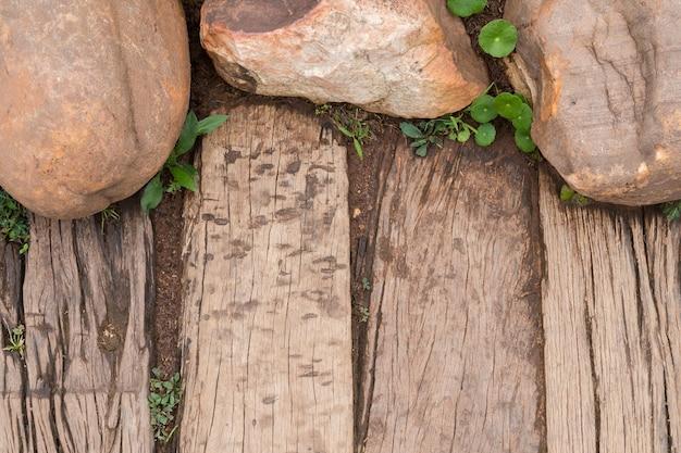 Vista superior da passagem de madeira no jardim decorado com a pedra e a árvore natural.