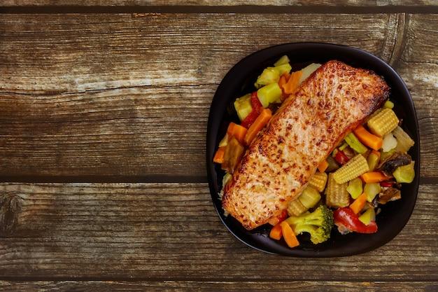 Vista superior da peça assada de salmão com legumes salteados asiáticos na placa preta.
