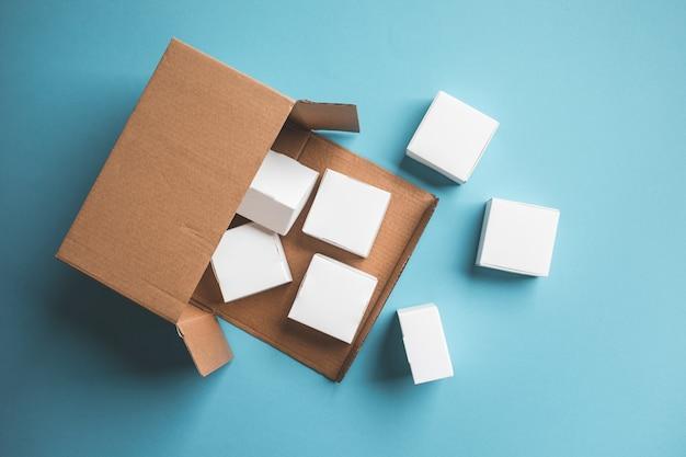 Vista superior da pequena caixa em fundo azul. conceitos de entrega ou compras online. compre e venda