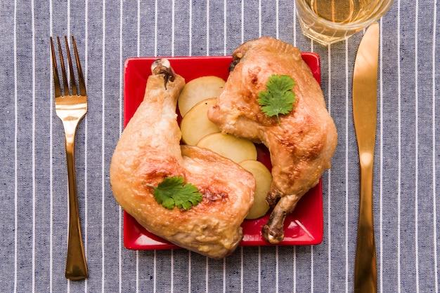 Vista superior da perna de frango assado gourmet no prato com garfo e faca de manteiga na toalha de mesa
