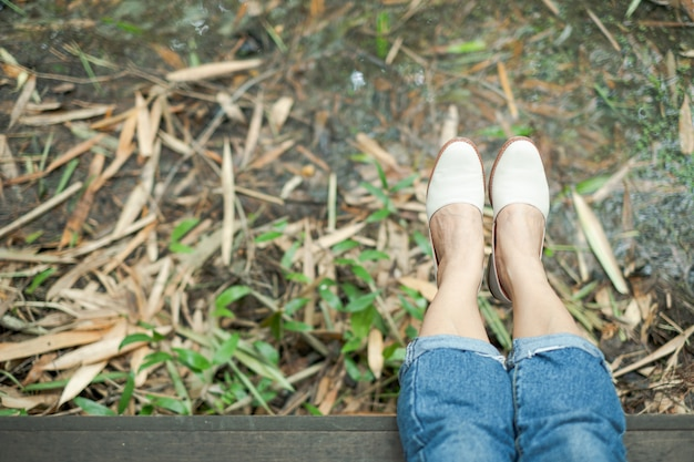 Vista superior da perna de mulher e sapato que sentado no cais de madeira