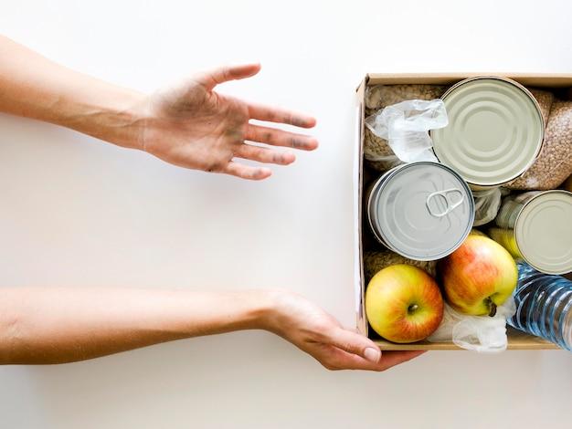 Vista superior da pessoa que recebe caixa de doação de alimentos