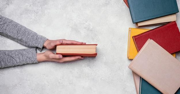 Vista superior da pessoa segurando o livro de capa dura