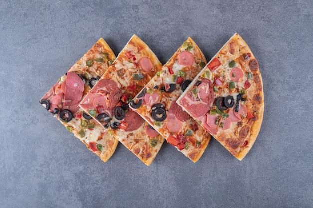 Vista superior da pilha de fatias de pizza de calabresa.