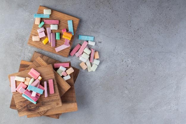 Vista superior da pilha de gomas coloridas em placas de madeira.