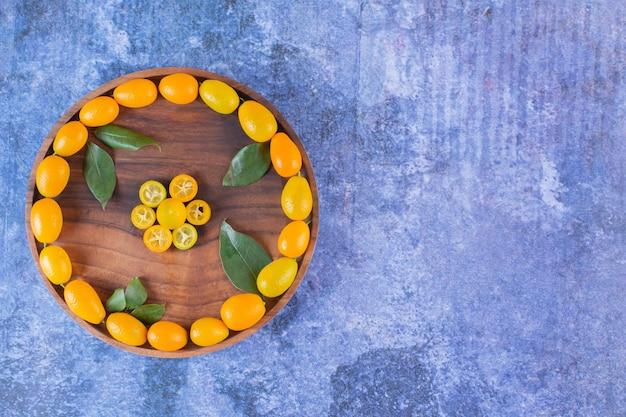 Vista superior da pilha de kumquats na bandeja de madeira.