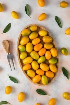 Vista superior da pilha de kumquats na placa de madeira
