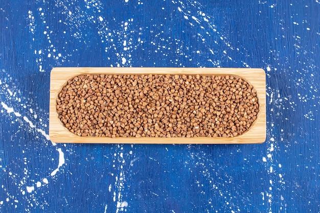 Vista superior da pilha de trigo sarraceno na bandeja de madeira sobre a superfície azul. .