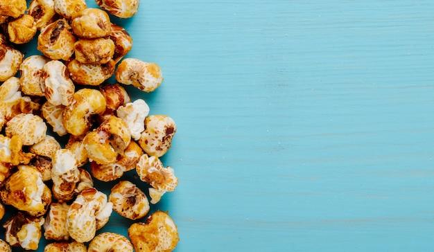 Vista superior da pipoca de caramelo doce espalhada sobre fundo azul, com espaço de cópia