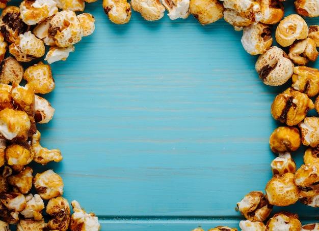 Vista superior da pipoca de caramelo doce sobre fundo azul de madeira, com espaço de cópia