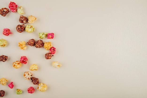 Vista superior da pipoca de skittles no lado esquerdo e branco com espaço de cópia