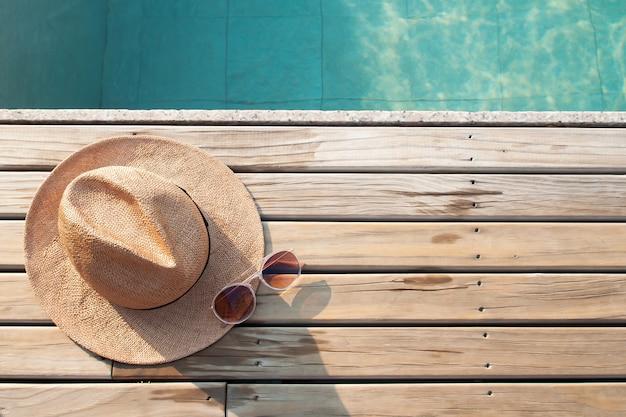 Vista superior da piscina, chapéu de sol e óculos de sol no chão de madeira